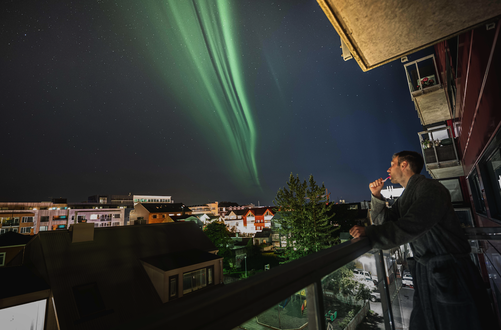 A man brushing his teeth under the Northern Lights in downtown Reykjavik
