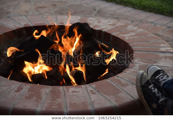 a warm fire pit and man with his feet up