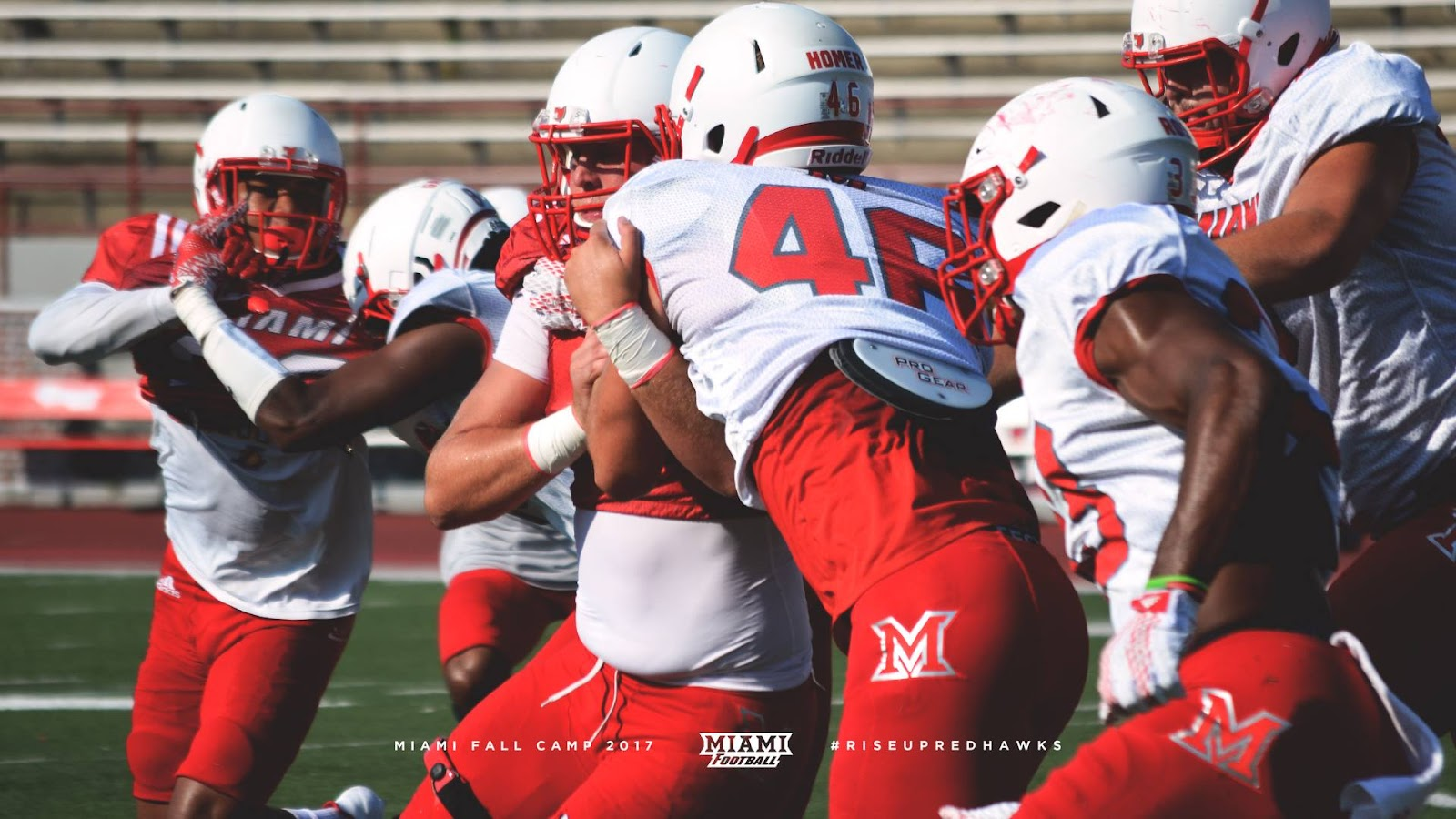 Miami RedHawks football players tackling each other during practice