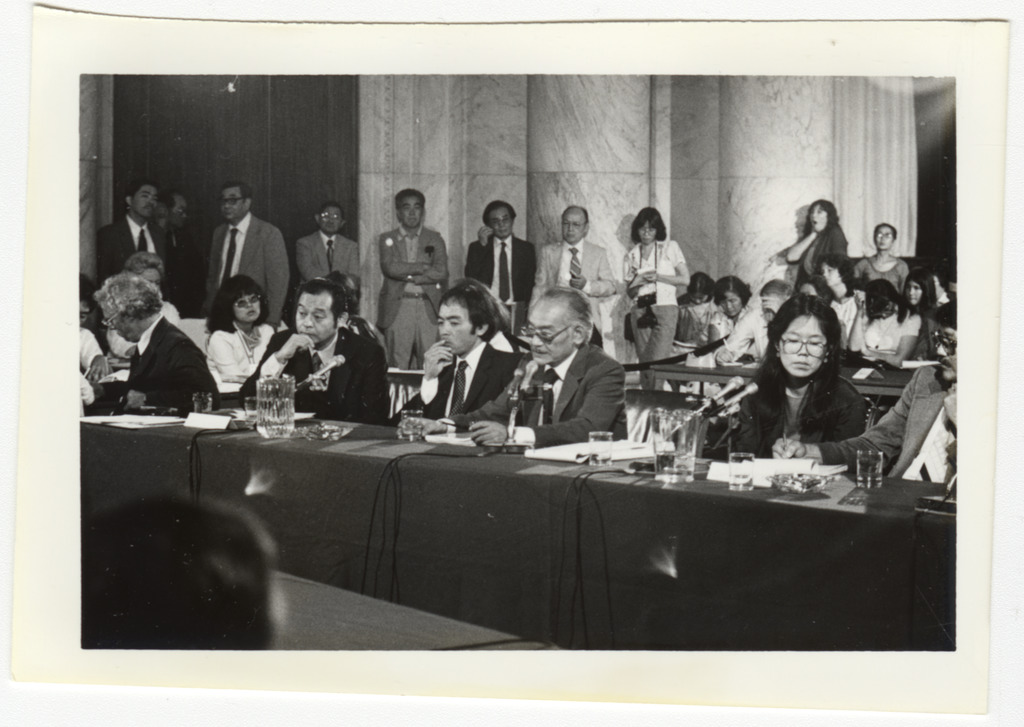 Japanese American witnesses seated at a table preparing to give testimony. There are microphones and glasses of water on the table and onlookers seated and standing against the wall behind them.