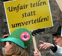 Demo mit Satire und Ironie, Schild (in Gold): »Unfair teilen statt umverteilen!«.