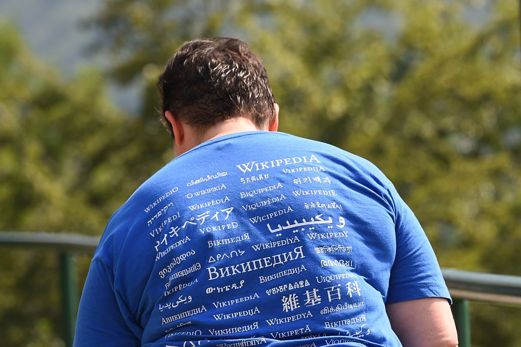 """A man attending the Wikimania 2016 meeting, wears a shirt reading """"Wikipedia"""" in different languages, at Esino Lario near Lecco on June 24, 2016. Google's reliance on Wikipedia helped the Chinese Communist Party spread official propaganda about the South China Sea to the English speaking world."""
