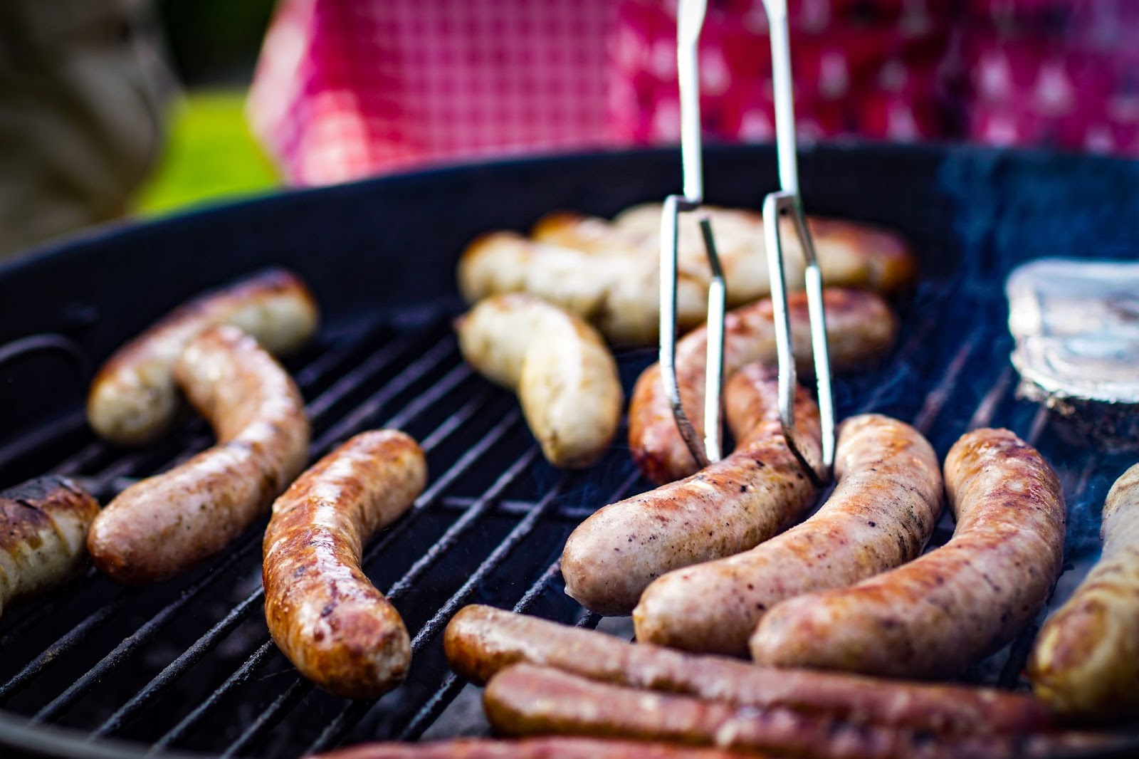 Different types of sausages being cooked on a grille.