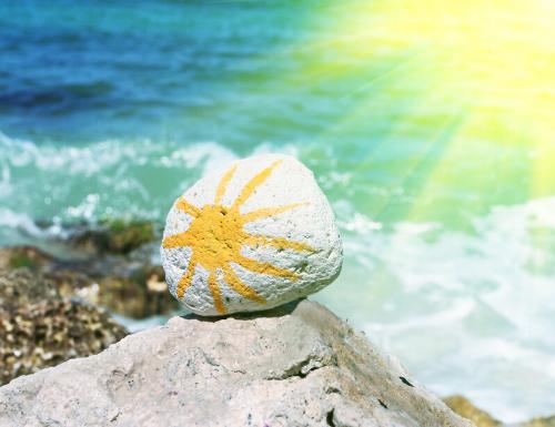 photo plage avec la mer et gros plan caillou avec un soleil dessiné dessus