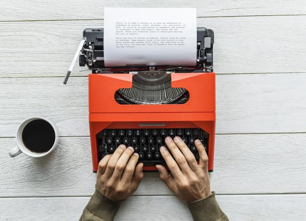 A imagem é composta por uma mão digitando uma história em uma máquina de escrever antiga de cor laranja.