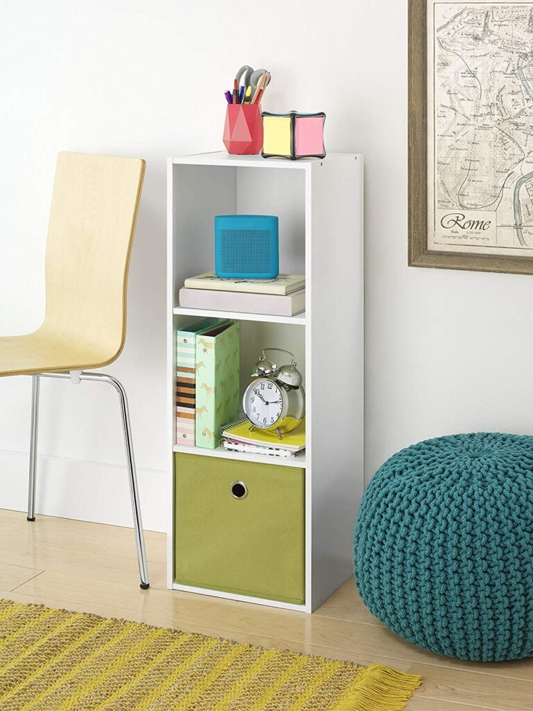 Best room organization tips - invest in cubes - white cube storage with green fabric bin next to a yellow chair and a blue ottoman