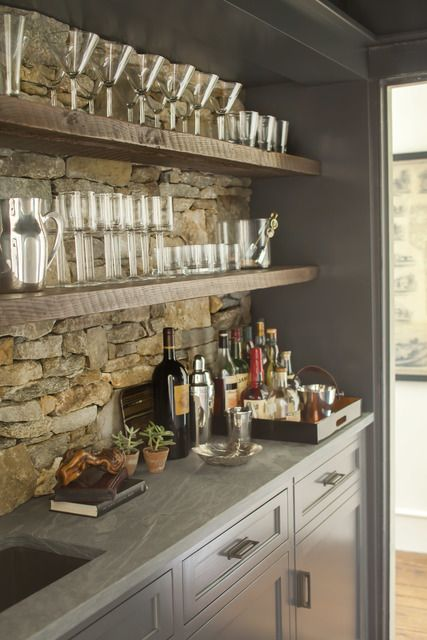 basement bar area with open shelving, stacked stone backsplash, grey shaker cabinets and sink