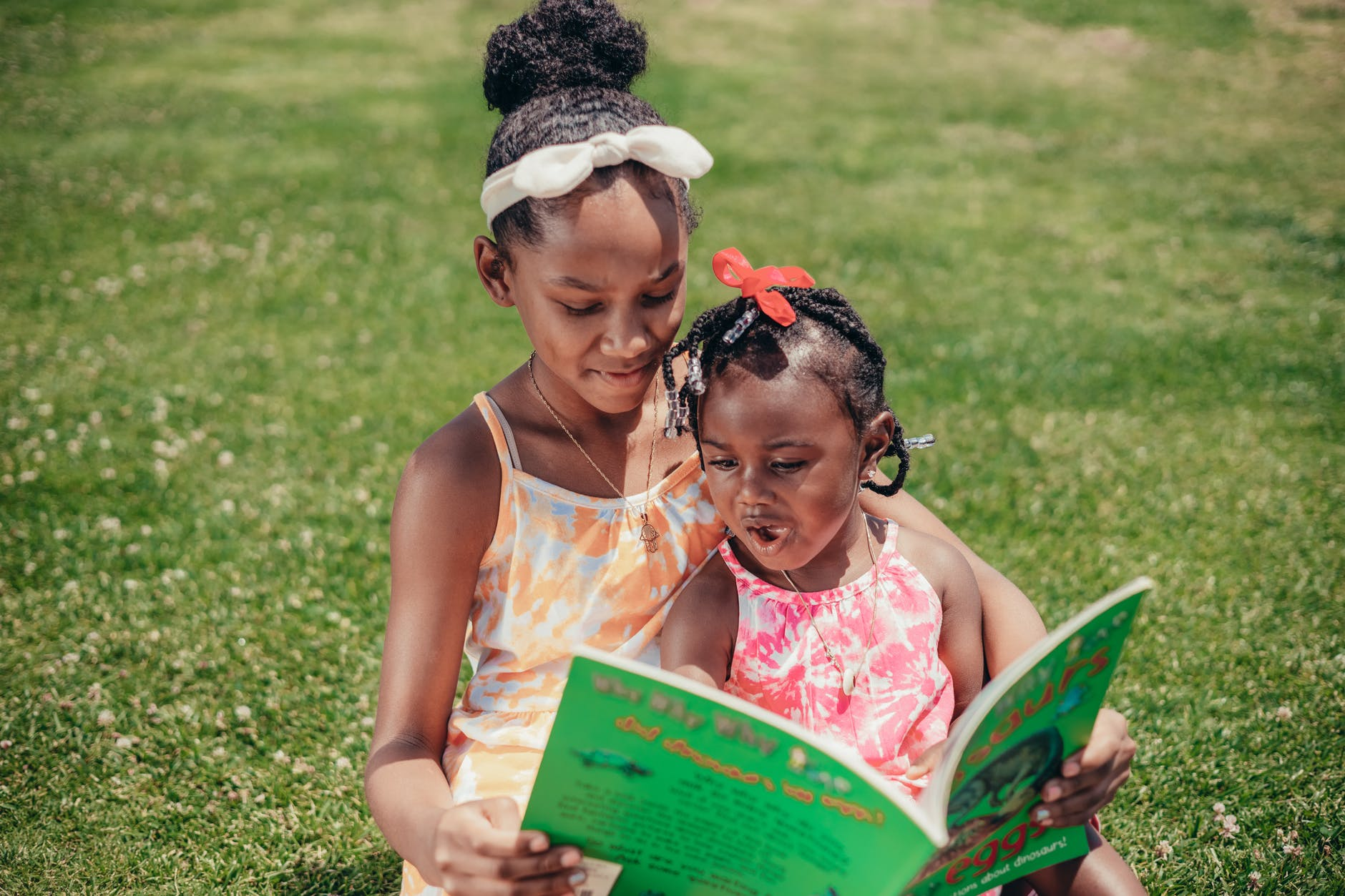 two children reading on a field