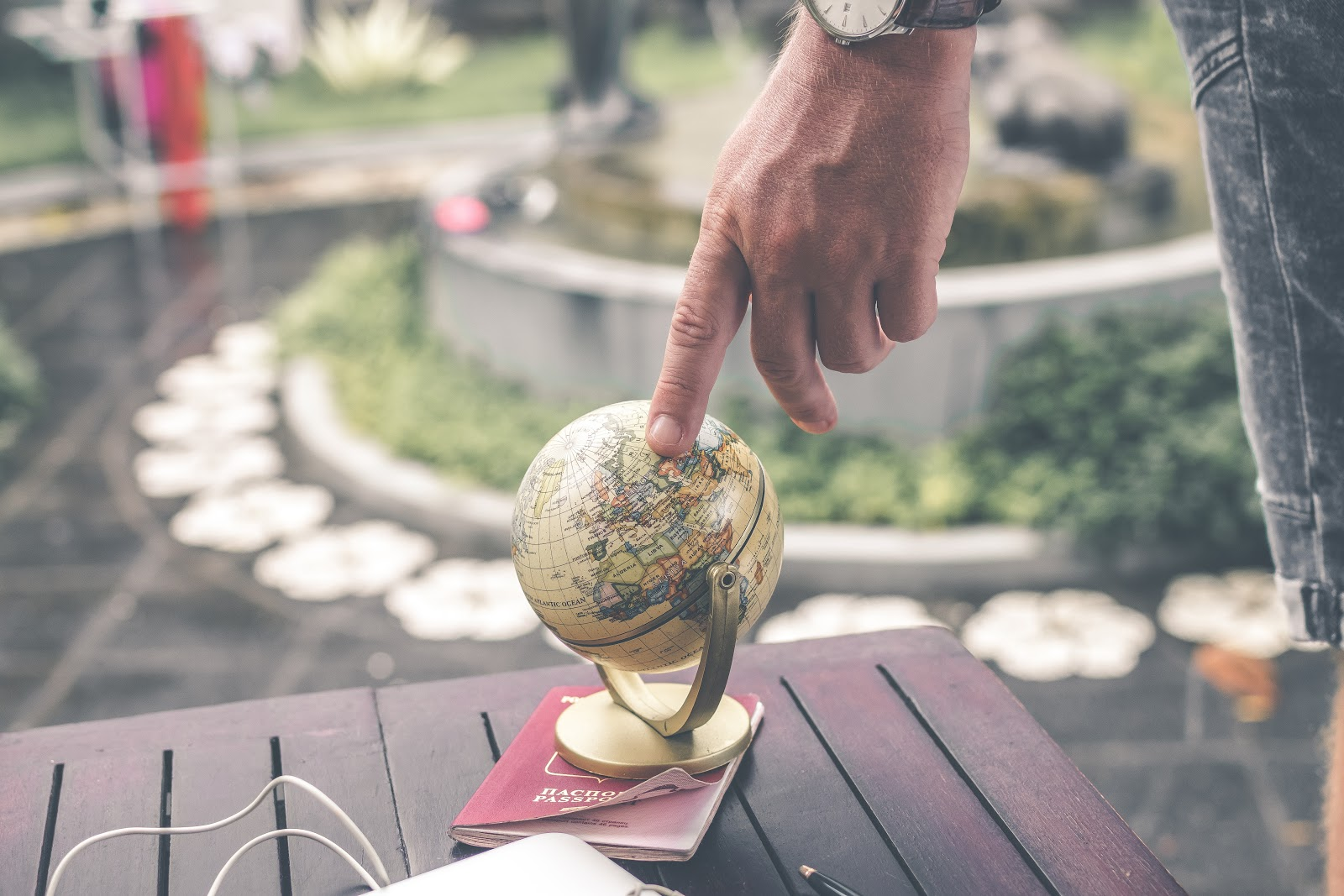 A finger pointing to a small globe. Learning how to speak a language can make the world a lot smaller!
