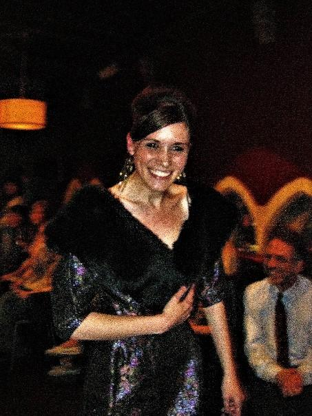 A shot of Jo in a dark sparkly dress with a fur or faux-fur collar. She has dangly earrings and a huge smile.