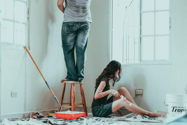 Two people painting a wall