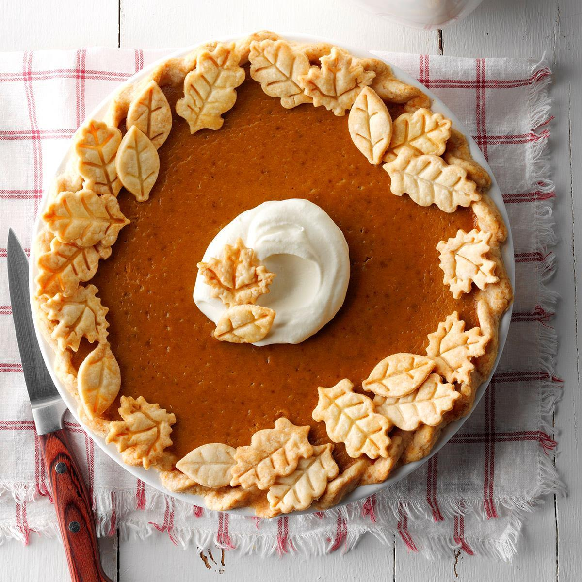 Pumpkin pie, complete with a dollop of whipped cream in the middle and with an edging of pie-dough autumn leaves