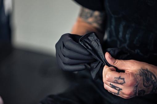 Artista De Tatuajes Poniéndose Guantes De Protección Foto de stock y más  banco de imágenes de Actitud - iStock