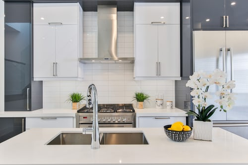 Benefits of Quartz Countertops; all-white kitchen with white and grey cabinets and stainless steel cooktop