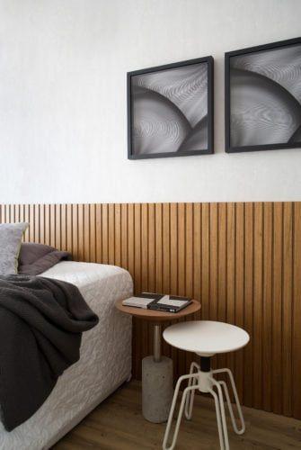 Painel de madeira ripada substituindo cabeceira da cama de casal com decoração minimalista, banquetas redonda, quadros decorativos preto e cinza.