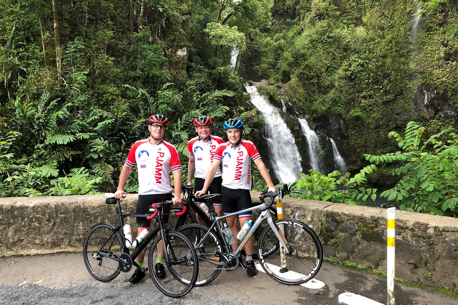 Cycling the Road to Hana - 3 PJAMM cyclists with bikes at waterfall