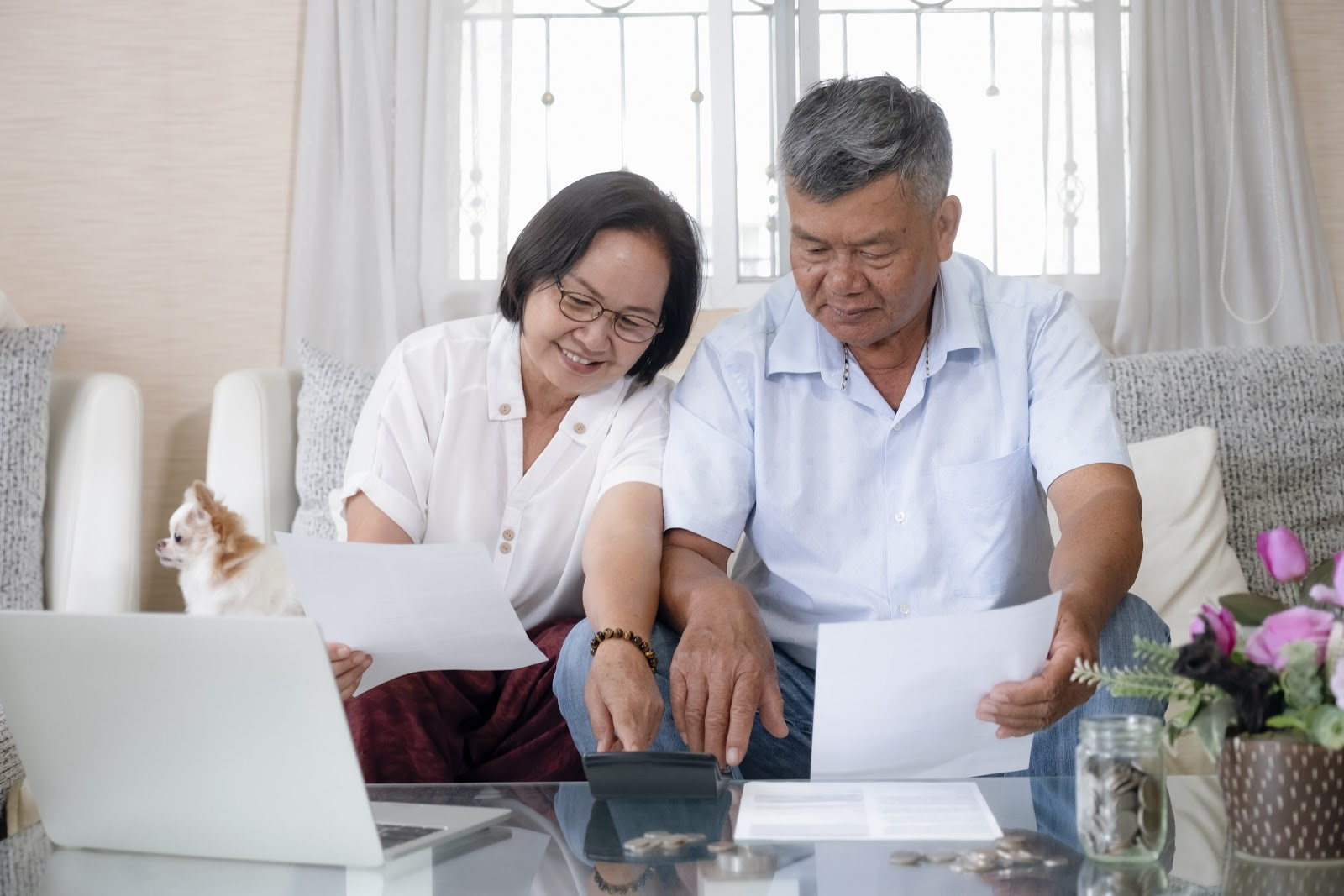 stocks that pay monthly dividends: Senior couple using a calculator while holding a white paper