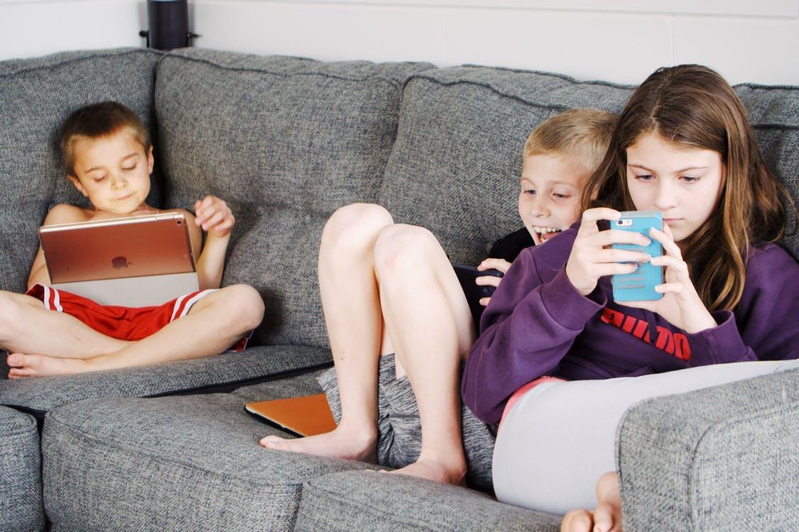 Positive barefoot children in casual wear resting together on cozy couch and browsing tablets and smartphones