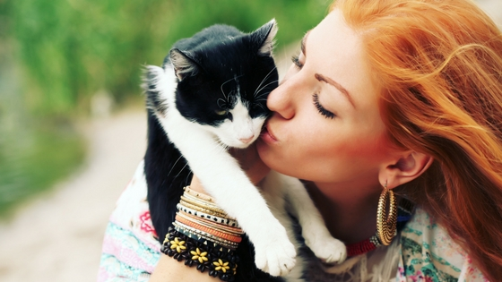 A woman kissing her black & white cat.