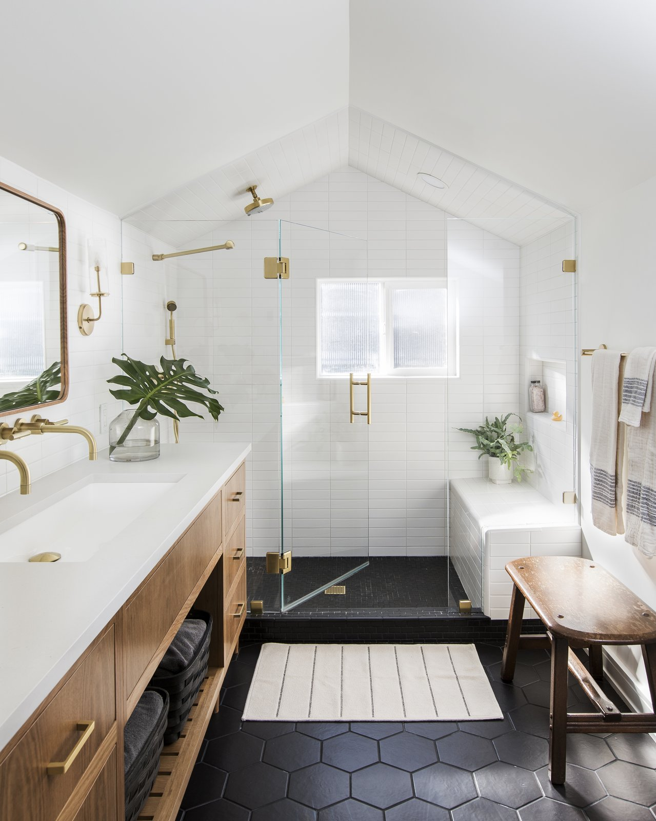 modern bathroom with pitched white ceiling, matte black hexagonal floor tiles, wooden vanity with white ceramic countertop