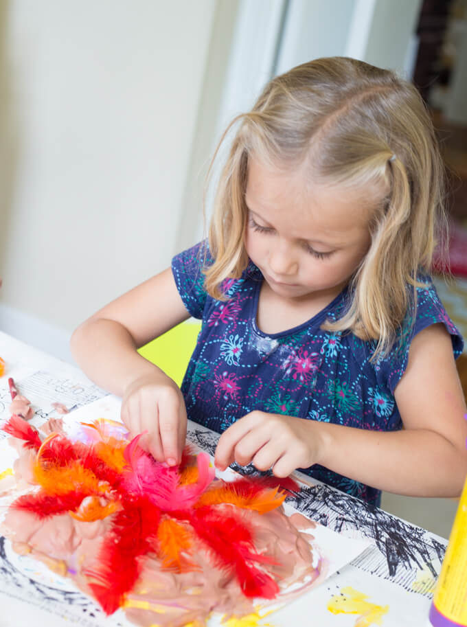 Child creating artwork with feathers.