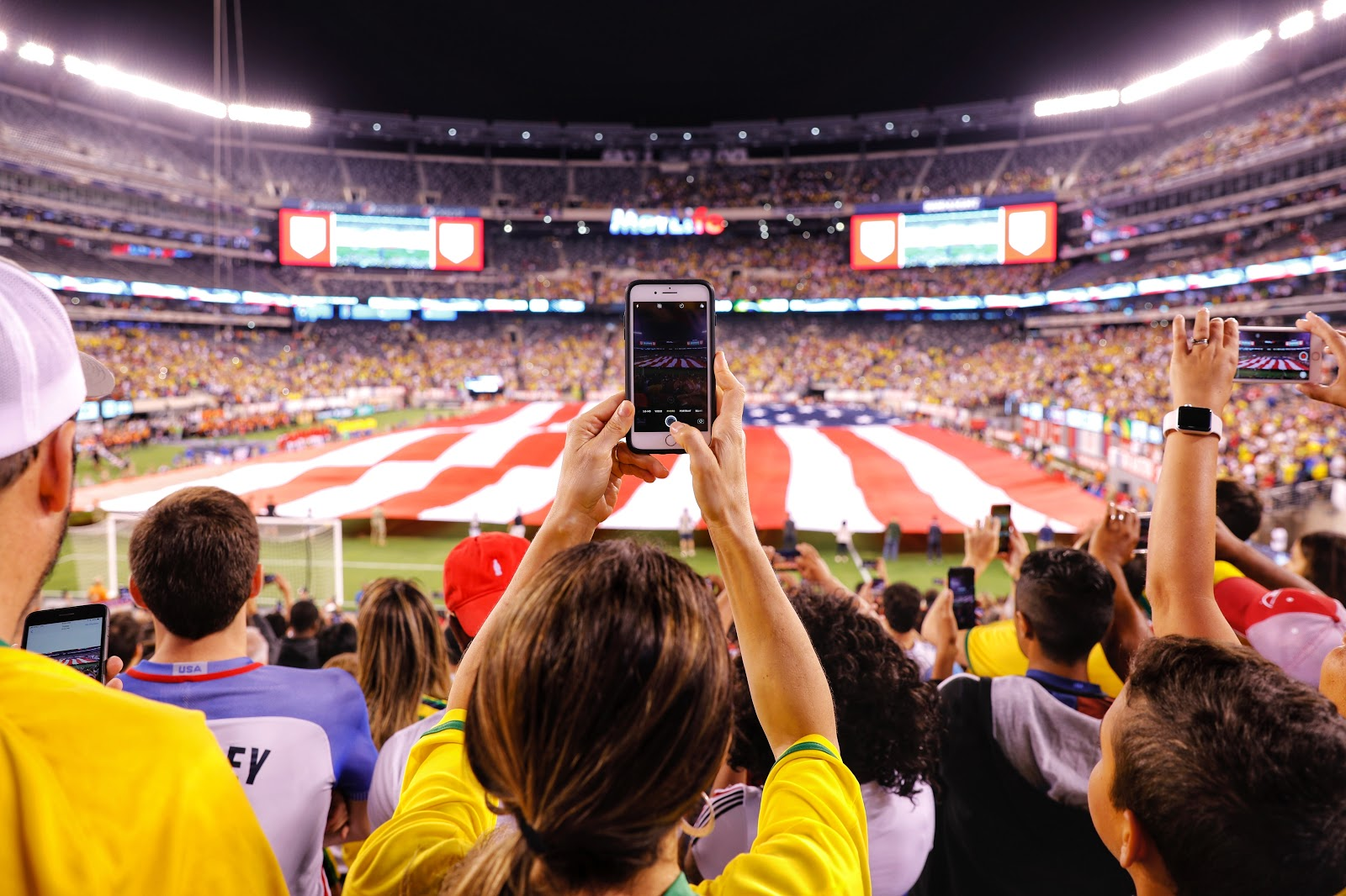 people in a crowd at a sporting event hold up their cell phones as a United States flag is held up over the field