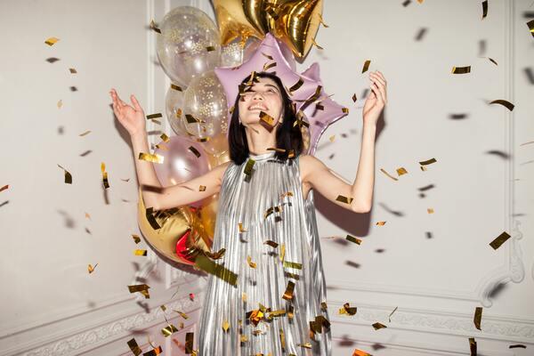 foto de uma mulher asiática celebrando com balões de fundo e papéis dourados sendo jogados nela