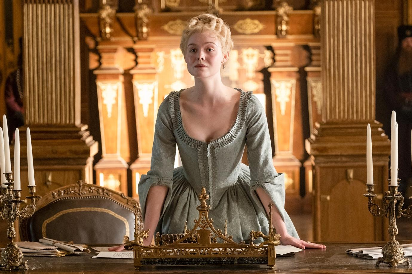 The Great (2020). Catherine the Great (Elle Fanning) is a young white woman in her 20s, with pale blonde hair done up in neat curls at the back of her head. She wears a pale grey-blue dress of the 18th century with elaborate sleeves, a deep neck-line, and large skirt. She is standing behind a large wooden table strewn with papers and framed by two large candelabras. Catherine is leant forwards with her palms planted on the table, assertive.
