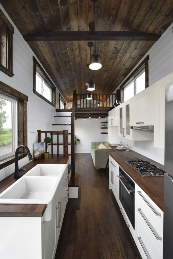 tiny house kitchen design ideas - dark wood floors, white cabinets, farmhouse sink, pitched roof, tiny home kitchen layout like hgtv tiny homes