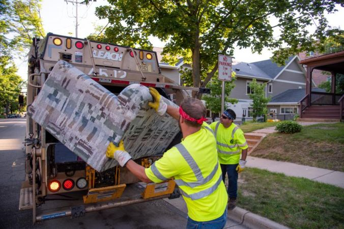 Two Streets employees putting a couch into a city collection truck