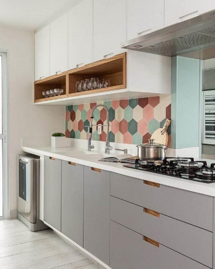 Cozinha com armários superiores brancos e com detalhes amadeirado e inferiores cinza com puxador amadeirado, bancada da pia branca, piso de madeira branca e azulejo na parede da pia hexagonal colorido.