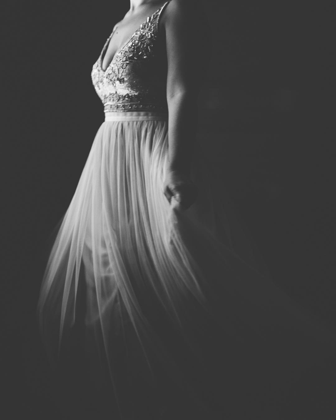 A black and white image of a bride wearing her wedding gown