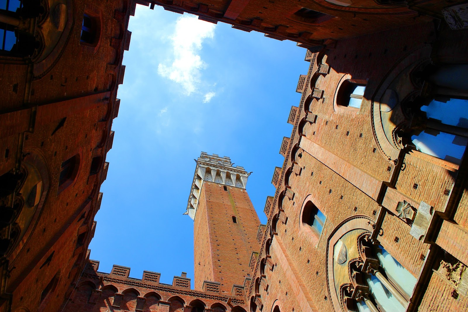 torre del mangia red brick medieval tower symnetrical photo seen from nearby square in siena italy