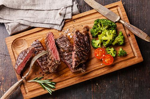 Meat and vegetables on a cutting board from Greensbury meat box delivery