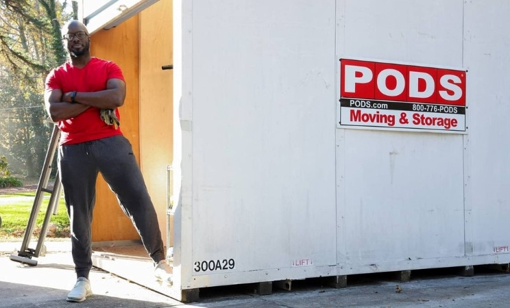 a man standing with a PODS Moving & Storage container