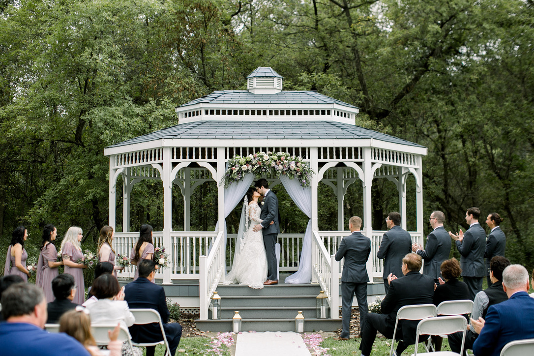 Couple getting married under A Touch of Class Event Center and Catering's outdoor gazebo.