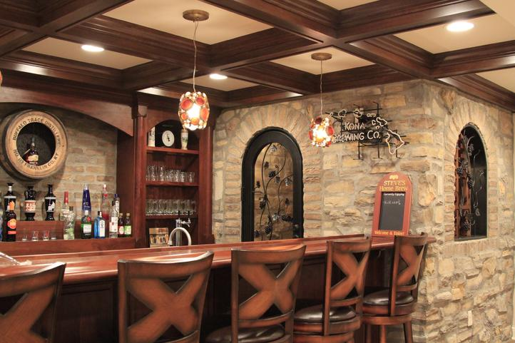 rustic basement bar with natural stone walls and warm wood bar top