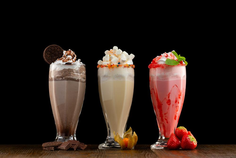 three milkshakes in glass cups