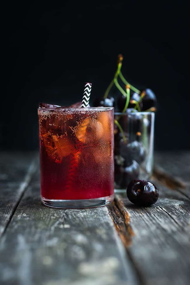 Bourbon and cola cocktail served on the rocks with a striped paper straw