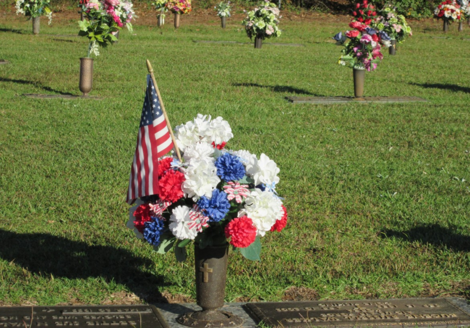 cemetery flowers and an American Flag