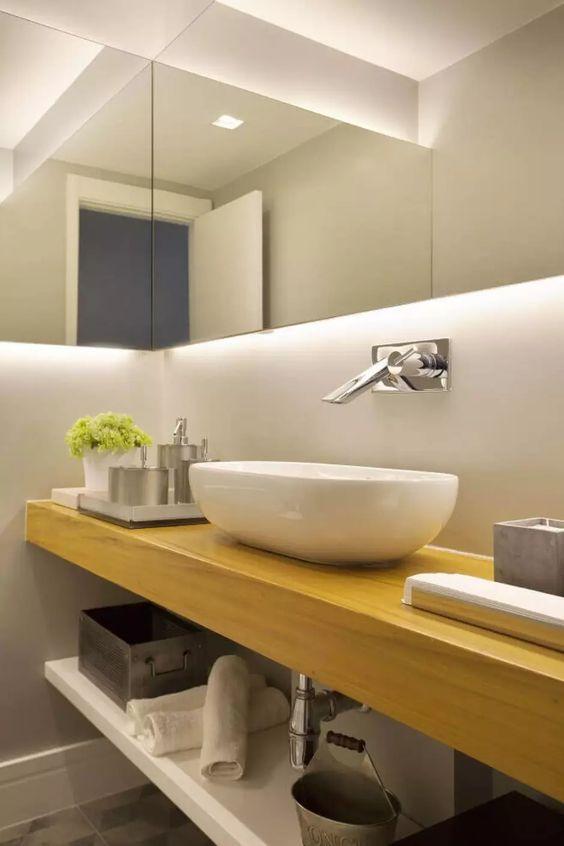 Torneira de parede monocomando  prata, bancada de madeira, cuba branca e acessório de lavabo.