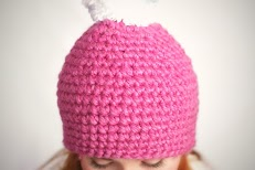 A girl with red hair wearing a pink beanie with white pom pom