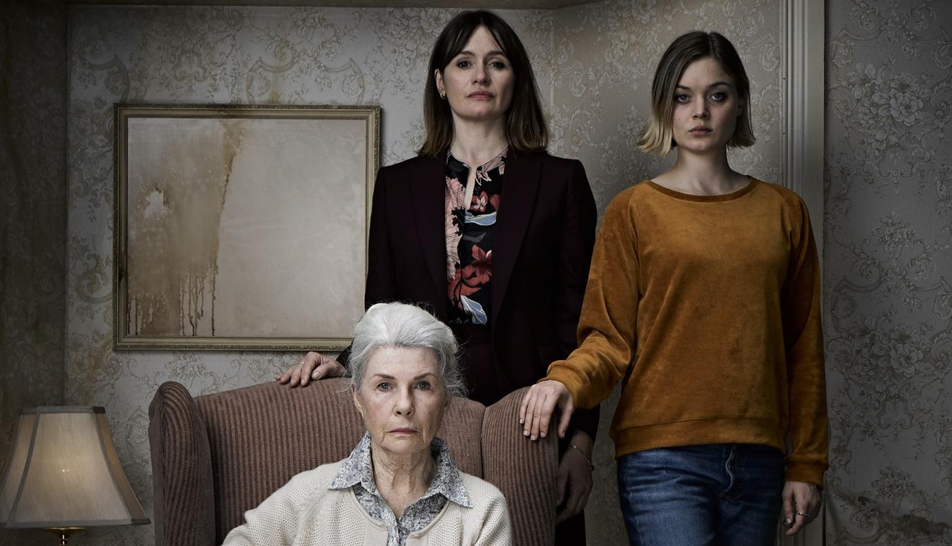 (L-R) Robyn Nevin, Emily Mortimer, and Bella Heathcote in Relic. The three women pose in a family portrait, looking directly at the camera with sombre expressions.