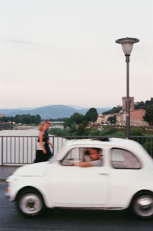 couple walking across bridge as car drives past