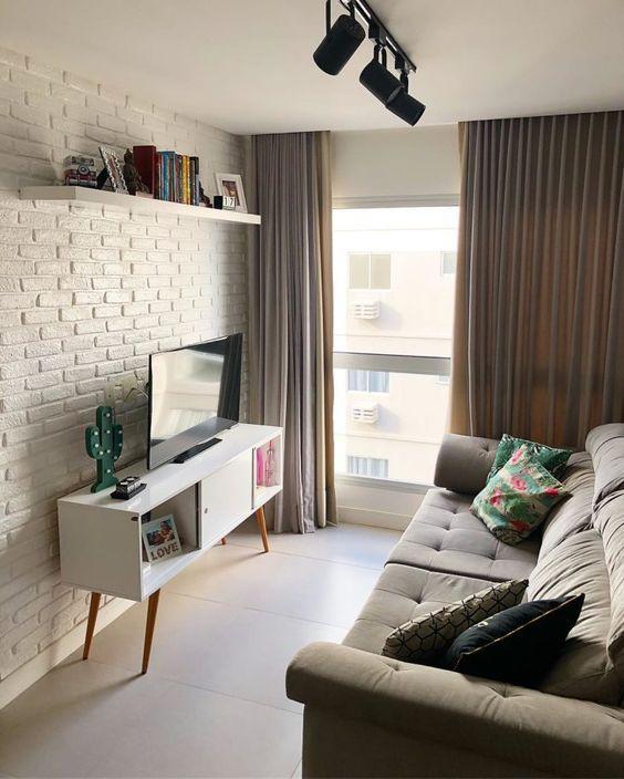 Sala minimalista com sofá cinza, almofadas coloridas, rack branca e janela com cortina.