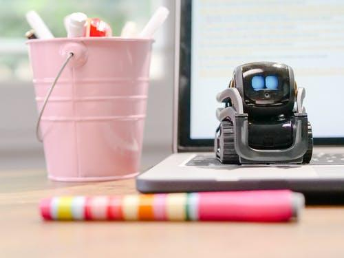 MIniature Toy Robot on Top of Laptop's Keyboard