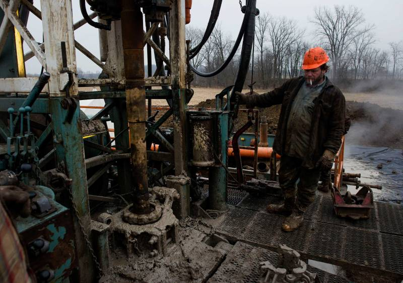 A rig hand works the controls while changing out a drill pipe at a Knox Energy Inc. oil drilling site in Knox County, Ohio, U.S., on Dec. 8, 2014.