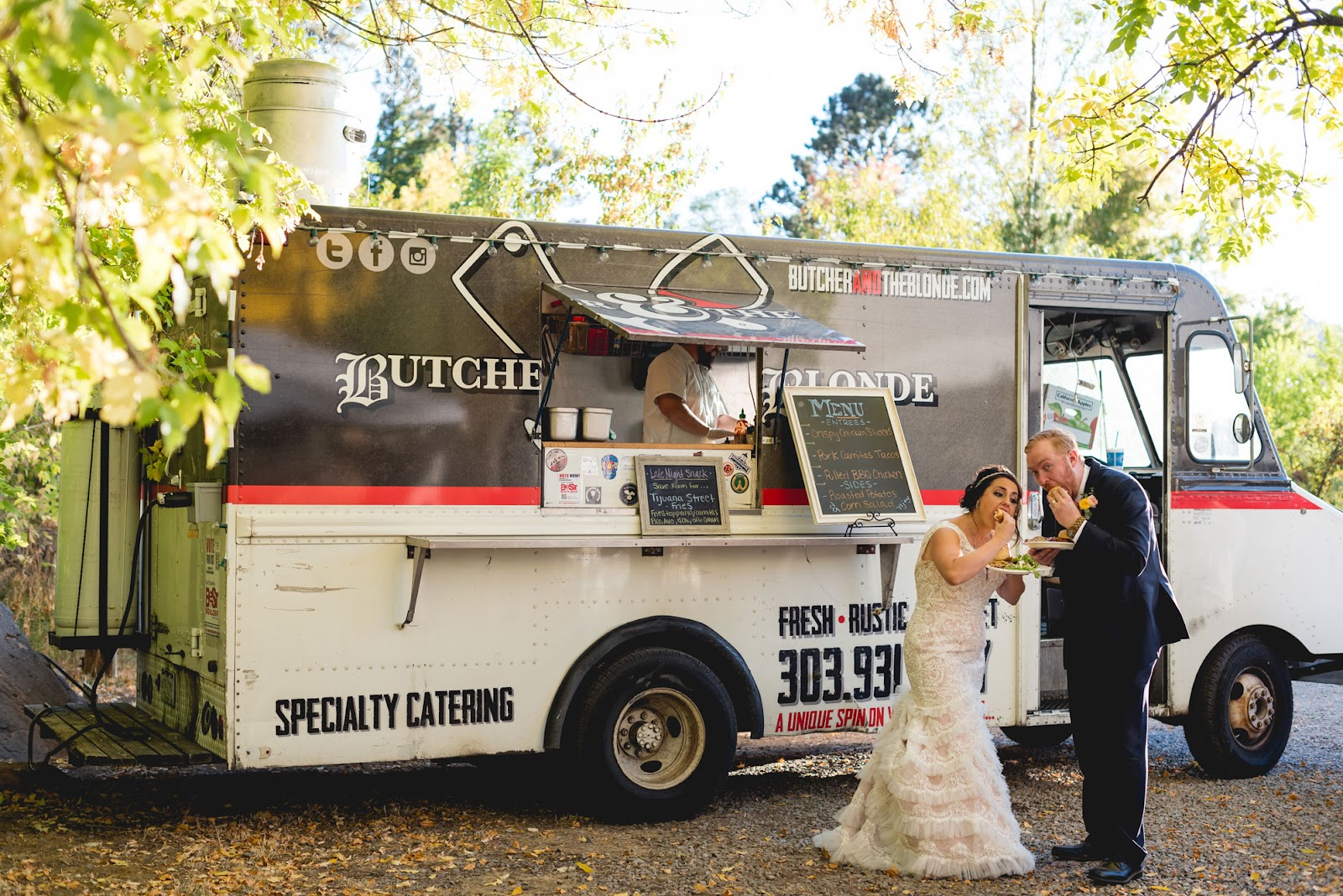 Bride and groom eating from a food truck at a wedding reception