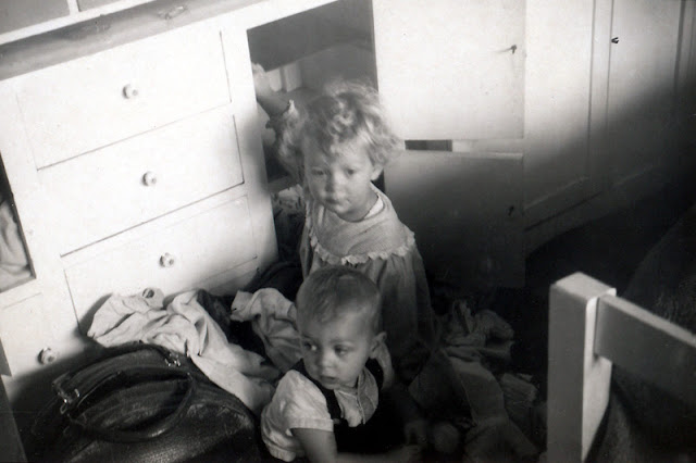 two young children beside a chest of drawers; the shelves are empty and clothes are all over the floor