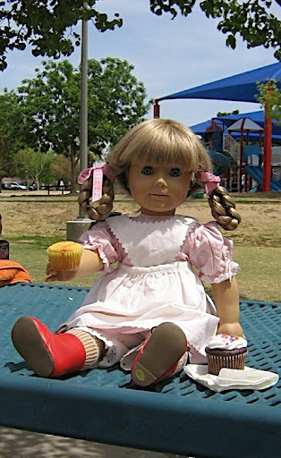 In a park, Kirsten, in her pink checked spring dress, holds up a cornbread muffin, with a chocolate cupcake with white frosting beside her.